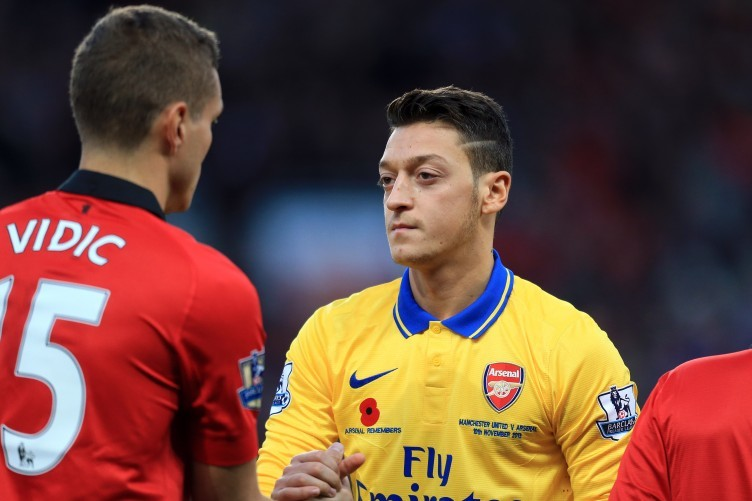 Manchester Untied captain Nemanja Vidic and Arsenal's Mesut Ozil.