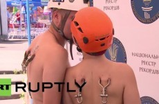 Couple cross a river by hooking a zip line to their back piercings