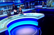 Dobbo makes an awkward dash for his chair on the Six One News