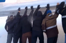 Watch Russian airline passengers push their frozen plane free from ice