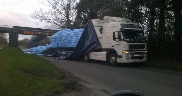 Lorry tries to make it under low bridge: Doesn't make it