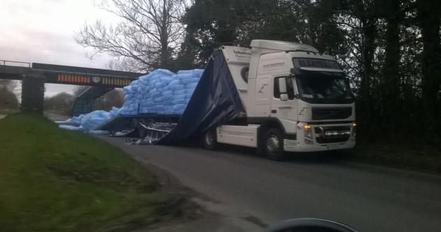 Lorry tries to make it under low bridge: Doesn't make it