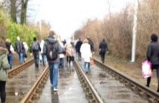 Passengers walk the track after power-cut stops some Luas trams