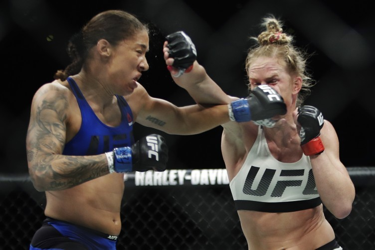 Germaine de Randamie, left, of the Netherlands, punches Holly Holm during a women's featherweight championship mixed martial arts bout at UFC 208