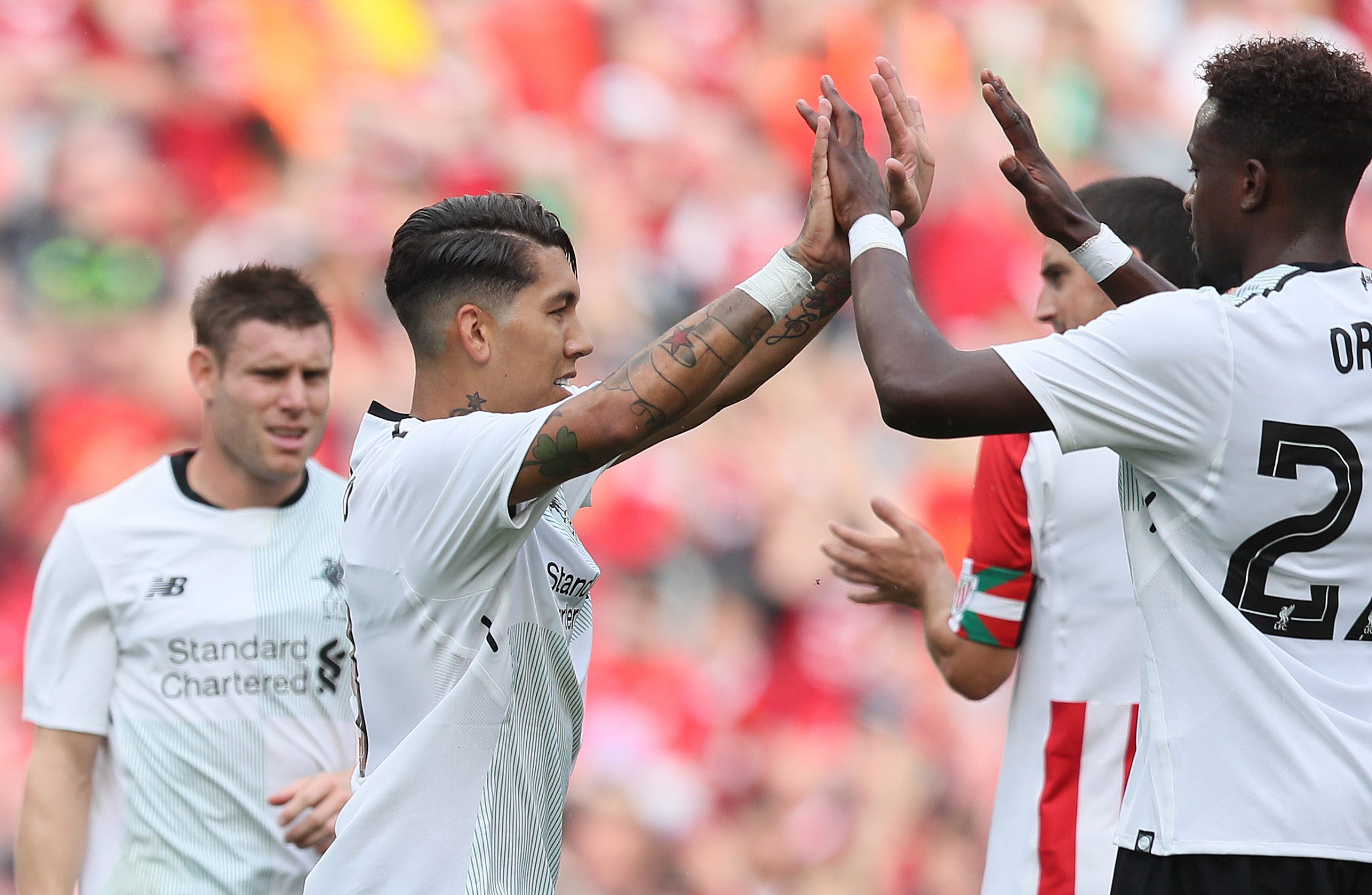 The Liverpool players congratulate goalscorer Roberto Firmino.                     Image PA Wire  PA Images
