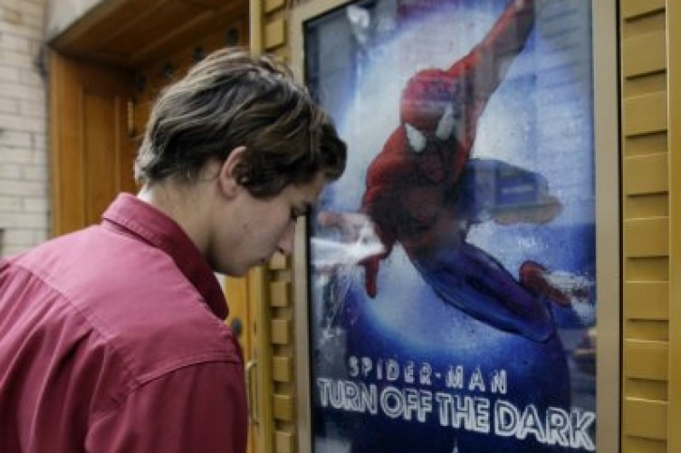 A theatre worker cleans an advertisement for the Spider-Man musical in New York
