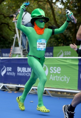 A runner in costume crosses the finish line