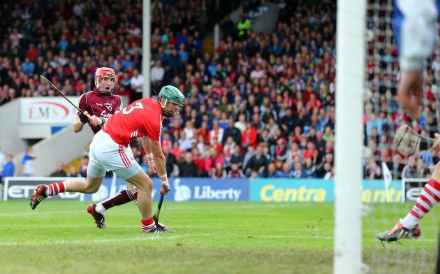 Conor Whelang scores a goal despite the efforts of Brian Murphy