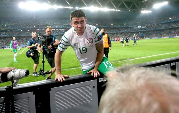 Robbie Brady jumps the advertising hoarding at the end of the game