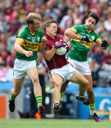 Donal O'Neill is tackled by Aidan O'Mahony and Donnchadh Walsh