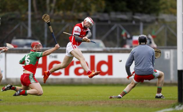 Con O'Callaghan scores a goal despite the tackle of Jim Fitzpatrick
