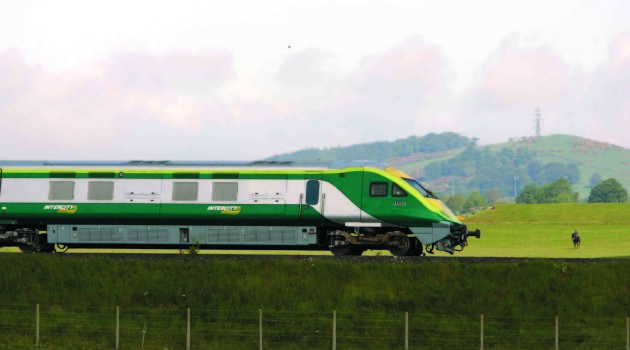2/6/2006 The new Irish Rail Mark 4 Train flys through the County Kildare countryside on its way to Cork City, with a horse and rider and Dunmurray hill in the background. Photo: Eamonn Farrell/Photocall Ireland.
