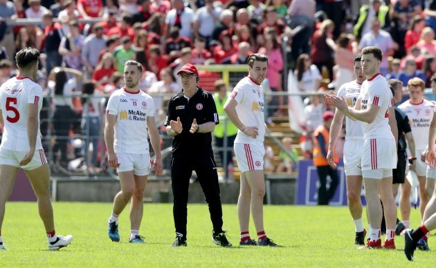 Mickey Harte calls his players in to talk on the pitch before heading in to the dressing rooms at half time