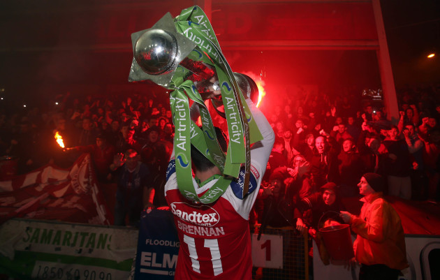Killian Brennan holds the trophy up in front of Pat's supporters