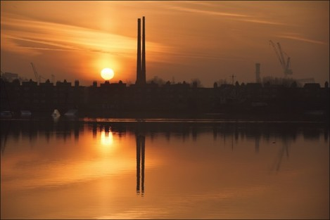 Poolbeg Chimney's silhouetted by sunrise