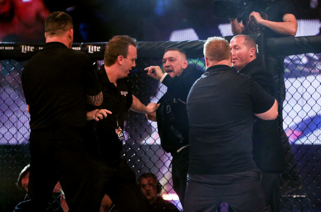 Conor McGregor is involved in a scuffle after the fight with referee Marc Goddard