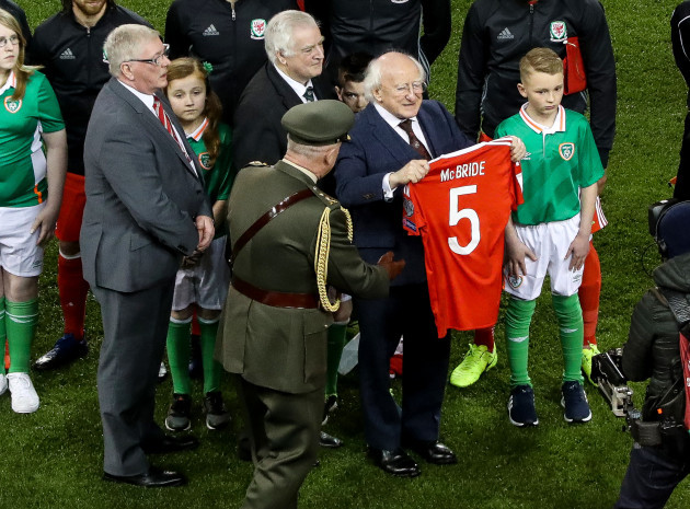 President Michael D Higgins holds up a jersey presented by Wales in tribute to Ryan McBride
