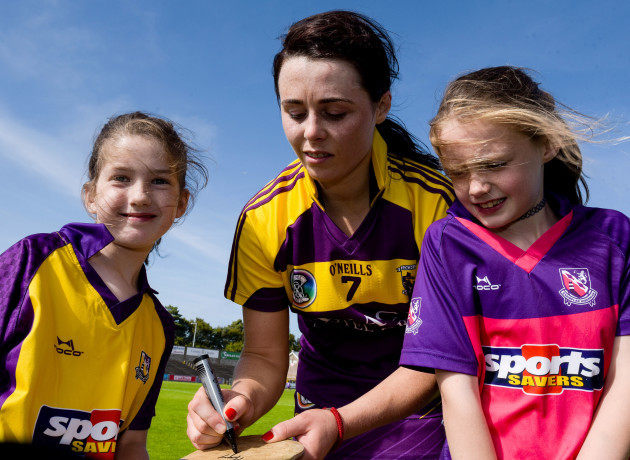 Mary Leacy signs hurleys for young fans after the game