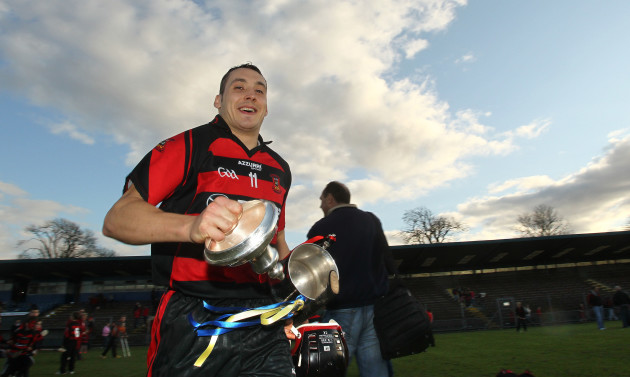 Shane O'Sullivan heads for the dressing room with the trophy after the game
