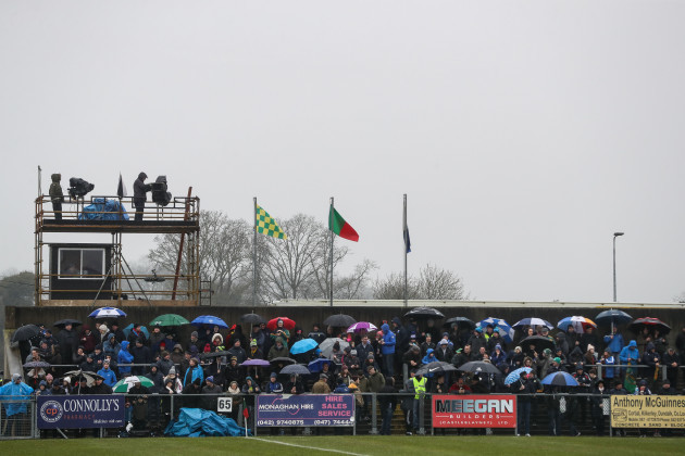 Fans await the start of the game in wet conditions