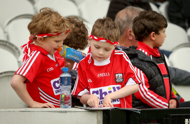 Young Cork fans read the programme before the game