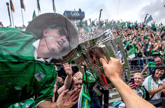 A Limerick fan kisses the Liam McCarthy Cup through the glass on Hill 16