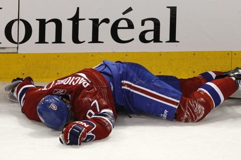 Montreal Canadiens' Max Pacioretty lies on the ice after taking a hit by Boston Bruins' Zdeno Chara.