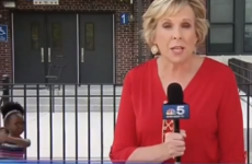 Little girl dances in the background of news report