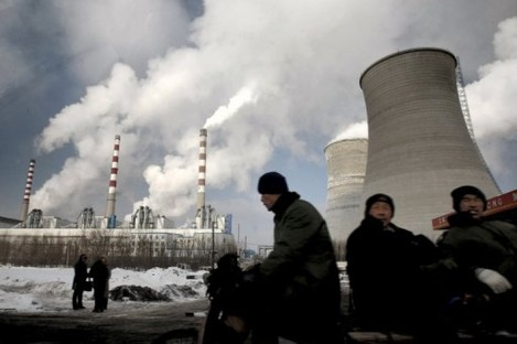 Workers cycle past a power plant on a tricycle cart in Changchun, in northeast China's Jilin province.