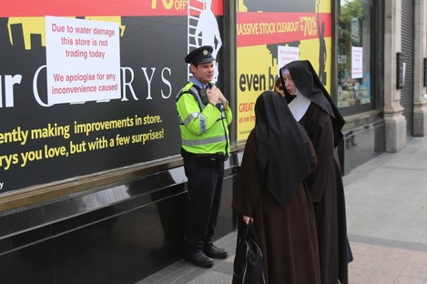 Two nuns talk to a garda outside Clerys department store which was closed due to water damage on Thursday