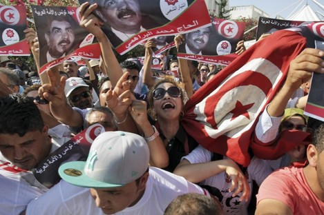 Tunisians react as the coffin of Tunisian opposition politician Mohammed Brahmi is carried out of his home in El Ghazela.