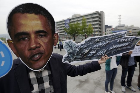 A protester wears a mask of Barack Obama during a protest at the US embassy in South Korea