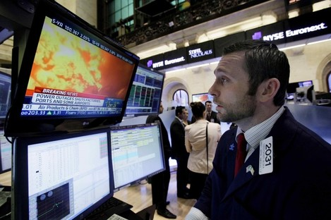 Specialist Christopher Gildea watches images from the earthquake in Japan on a television screen at his post on the floor of the New York Stock Exchange