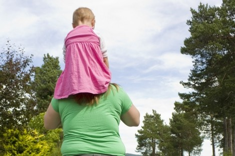 Obese mother carrying daughter on shoulders, exercising