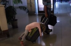 Little girl falls asleep on wheely case after a long flight
