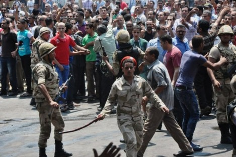 Egyptian security forces try to keep angry crowds away from the al-Fatah mosque