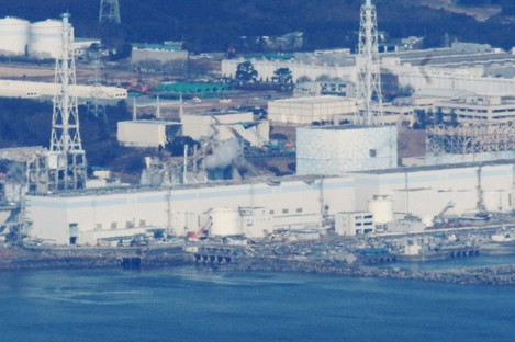 An aerial photograph of the Fukushima I plant, taken while engineers attempted to drop water on it from helicopters.