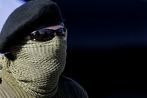 A masked dissident attends Ryan's funeral last year
