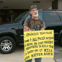 Man forced to hold 'IDIOT' sign outside police station