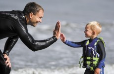Three-year-old surfer kid rides waves and gives high five