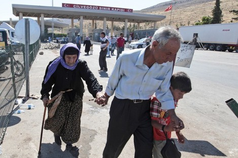 Syrian refugees arrive at the Turkish Cilvegozu gate border earlier today.