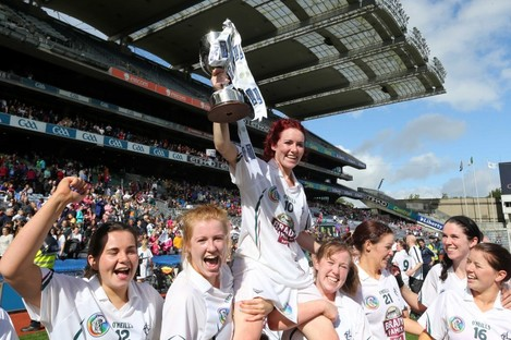 Kildare captain Clodagh Flanagan is carried by her teammates as she holds up the cup.