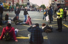 Protesters sit down and block cars on O'Connell Bridge and the Quays
