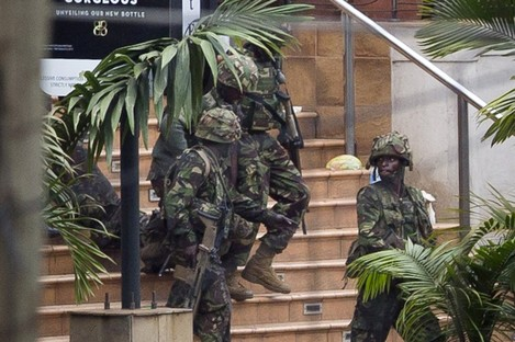 Soldiers from the Kenya Defense Forces carry a wounded colleague, following the sound of explosions and gunfire, out of the Westgate Mall in Nairobi, Kenya.