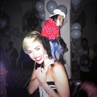 Miley Cyrus poses with a monkey dressed as a cowboy on her back