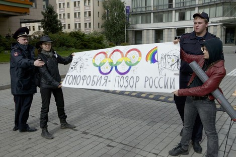 """Russian police officers detain two gay rights activists holding a poster reading """"Homophobia is Russia's Disgrace"""" during a protest this week."""