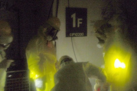 TEPCO employees work to restore power at the control room for Reactors 1 and 2 on Wednesday.