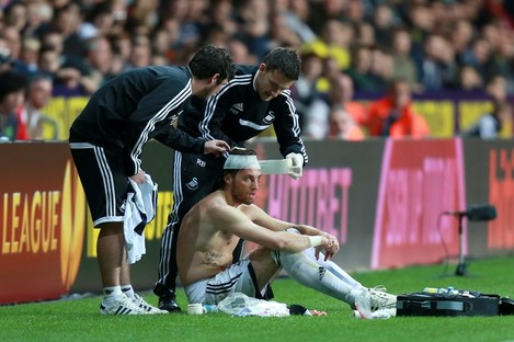 Swansea striker Michu receives attention after picking up a head injury.