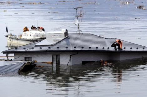 Divers search a house today which was swept into the sea by the 11 March tsunami.