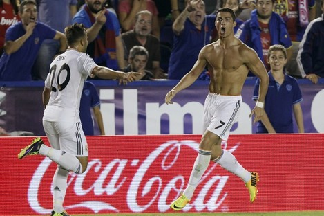 Real Madrid's Cristiano Ronaldo, right and topless, is congratulated by teammate Jese Rodriguez.